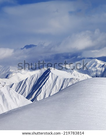 Top of off-piste snowy slope and cloud mountains. Caucasus Mountains, Georgia, ski resort Gudauri. - stock photo