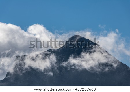Top of Slovak national mountain called Krivan in High Tatras - blue sky and white clouds - detail from Slovak mountains, Europe