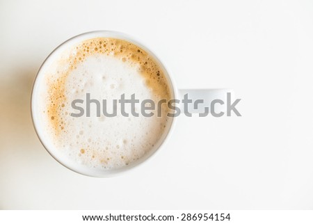 Top of view coffee cup on white table with hard light from side window