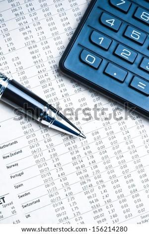 top of view of a business pen near a calculator on financial newspaper under light tint blue  - stock photo