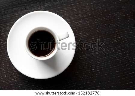 top of view of a white cup with coffee with space for text over wood black table - stock photo