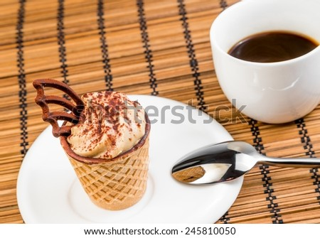 top of view of delicious little coffee cake with chocolate near a cup of coffee on wood background