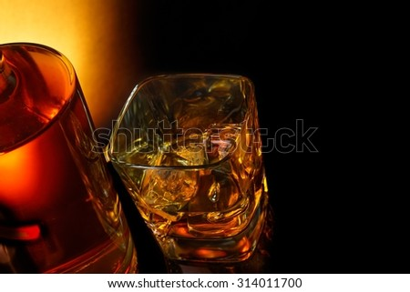 top of view of glass of whiskey near bottle on black table with reflection, time of relax with whisky
