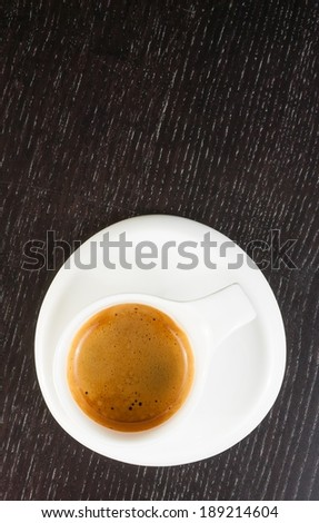 top of view of great italian coffee in a white cup, close-up shot on good foam on black wood table - stock photo
