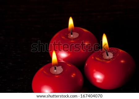 top of view of red christmas candles on black wood table background with space for text