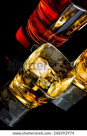 top of view of whiskey with ice in two glasses on black background, with reflection - stock photo