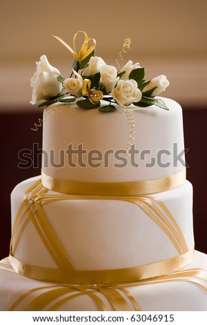 Top of Wedding Cake Decorated with Roses and Gold Ribbon - stock photo