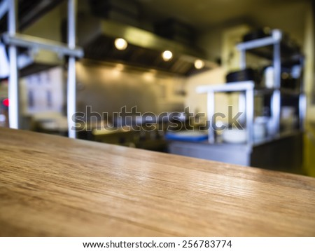 Top of Wooden counter with Blurred Kitchen Restaurant Interior Background - stock photo