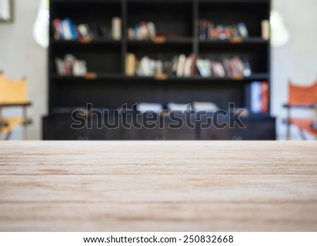 Top of Wooden Table with Blurred Book Shelf Modern Interior Background - stock photo