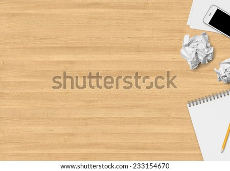Top office table with papers, crumpled papers, note, pencil and smartphone - stock photo