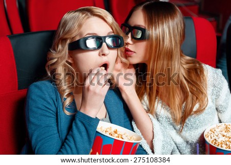 Top secret. Two pretty girls in cinema, one of them telling her secret to another one that eating popcorn. - stock photo