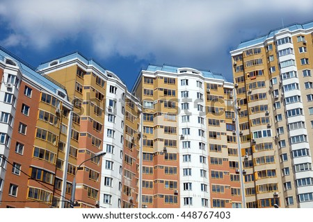 Top section of modern apartment buildings constructed from bricks over clear blue sky with white clouds on summer day