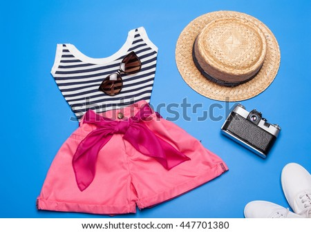 Top, shorts, hat, photo camera and shoes - collection of summer woman clothes and accessories - stock photo
