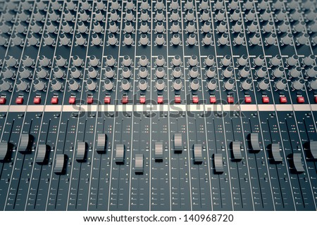Top shot of a mixing console, equipped in various sliders, switches and adjusters. It is used for audio signals modifications to achieve the desired output. - stock photo