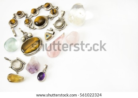 Top shot of handmade silver pendants with tigers eye, pearl, gold, rutilated quartz, rose quartz, citrine, precious stone  on white background, close up, isolated, space for text, selective focus