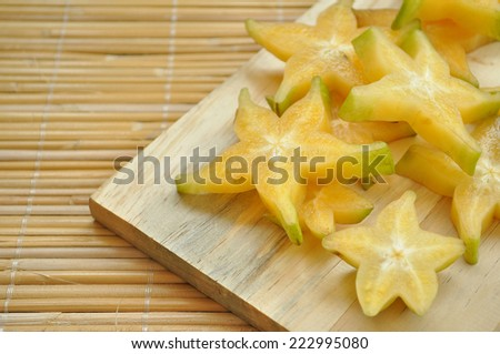 Top shot of starfruit on a wooden chopping board with space on the left side - stock photo