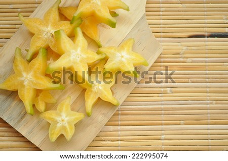 Top shot of starfruit on a wooden chopping board with space on the right side - stock photo