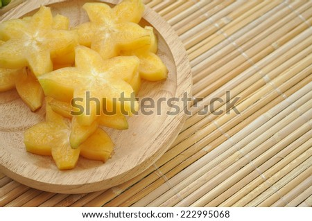 Top shot of starfruit on a wooden plate with space on the right side - stock photo