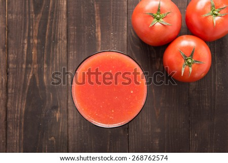 Top shot vegetable smoothie made of red ripe tomatoes on wooden table - stock photo