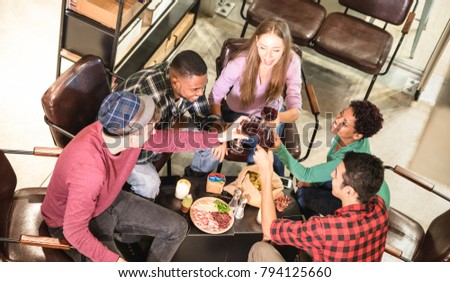 Top side view of multi racial friends tasting red wine and having fun at cool fashion bar winery location - Multicultural trendy friendship concept with people enjoying time out drinking together