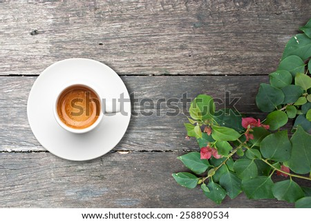top view a cup of espresso coffee with wooden table and some green leafs - stock photo