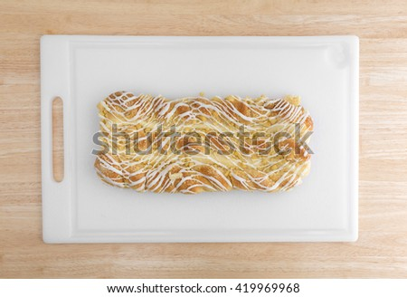 Top view a large cheese danish on a plastic cutting board atop a wood table top. - stock photo