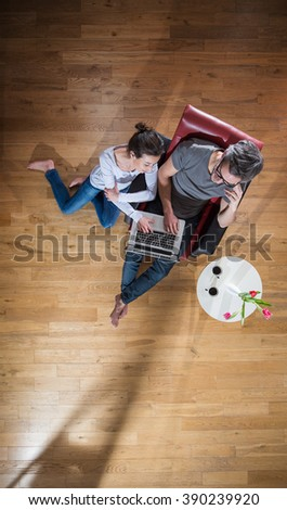 Top view, A  stylish couple sitting in the living room using a laptop, man sits in an armchair, the woman on the wooden floor. A little table with flowers and two cups of coffee near them - stock photo