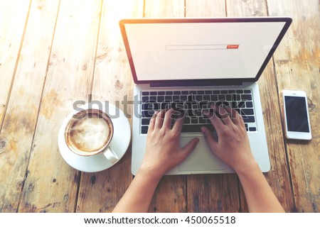 Top view (above) of beautiful young hipster woman's hands busy working on her laptop sitting at wooden table in a coffee shop - retro filter effect and vintage color style - stock photo