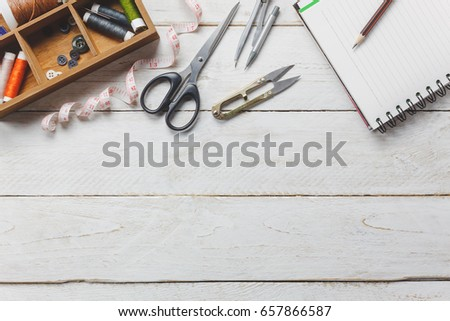 Top view accessories tailor concept.Tailor tools is cutting scissors, spools of thread,tape measurement,buttons and sewing clothes. Notebook for free space text on rustic wooden background.