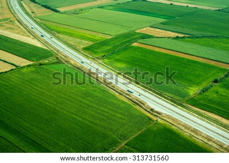 top view, aerial photos, and road cars moving in the green fields of summer - stock photo