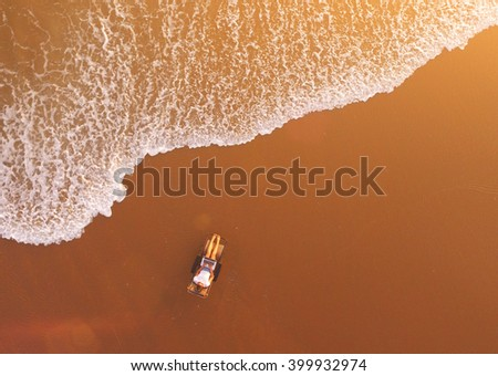 Top view air shooting from remote drone of a woman traveler is watching movie on laptop computer, while is relaxing on beach near sea with copy space background for your advertising text message - stock photo