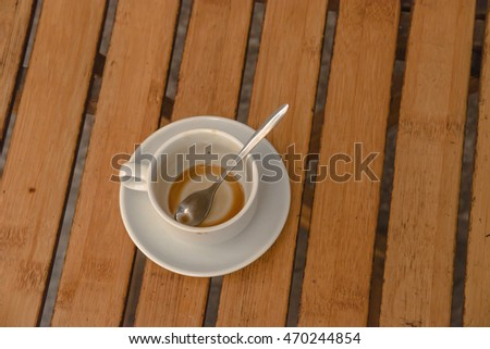 Top view an empty traditional Vietnamese milk coffee in white ceramic cup and saucer on outdoor wooden table.Top view a morning Vietnamese gourmet coffee cup. Food concept.