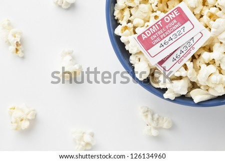 Top view and cropped image of a pop corn bowl with movie tickets above and scattered pieces on a white background - stock photo