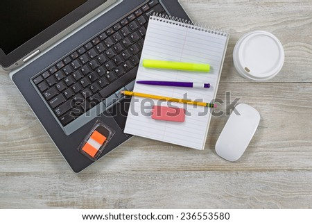 Top view angle shot of home office wooden desktop with various items including: laptop, coffee paper cup, notepad, pen, pencil, eraser, marker, and mouse.  - stock photo