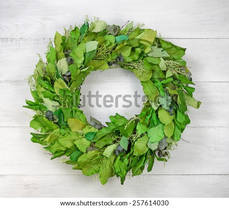 Top view angled shot of seasonal wreath made of green leaves on white aged wood - stock photo