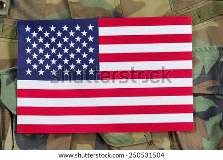 Top view angled shot of United States flag with military uniform background.   - stock photo