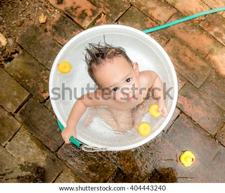 Top view Asian baby boy outdoor bathing in the white bathtub . He is smiling and playing yellow duck full of happiness, Country side culture of Thailand - stock photo