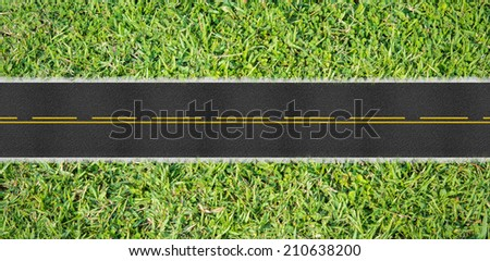 Top view asphalt road on the green grass - stock photo