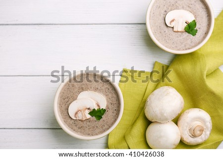 Top view at delicate cheese cream soup with mushrooms and green napkin on a white wooden table. - stock photo