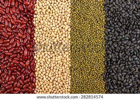 Top view background of different varieties of beans: red kidney beans, soybeans, mung beans, black beans - stock photo