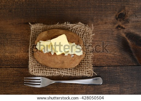 top view baked potato with butter and fork