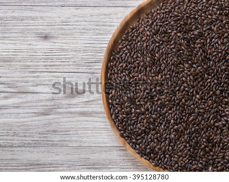 Top view - Beer ingredient, Chocolate malt in wooden plate and on wooden background - stock photo