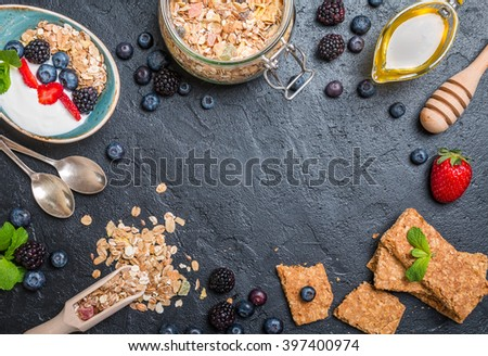 Top view blackboard with copyspace from granola bars and healthy homemade granola with toasted oats, yogurt, honey and berries. Health and diet concept. - stock photo