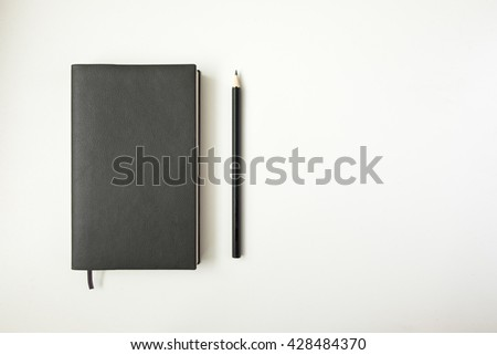 Top view blank black leather diary and pencil on white desk - stock photo