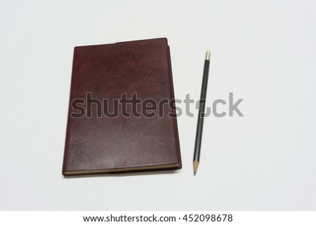 top view blank brown leather diary and pencil on white background - stock photo