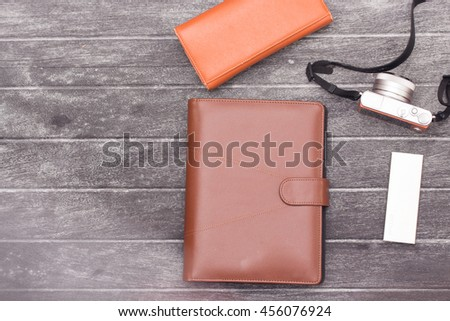 top view blank orange leather diary and pencil on white desk - stock photo