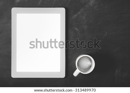 top view blank screen touchpad and coffee cup with copy space on black board for background - stock photo