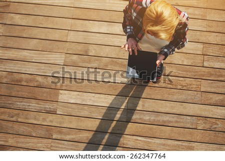 Top view blonde hair young woman using digital tablet with with a blank screen standing on wooden floor with copy space area background, young freelancer using busy tablet outdoors - stock photo