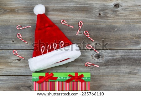 Top view close up of candy canes, gift and Santa hat placed on rustic wood  - stock photo