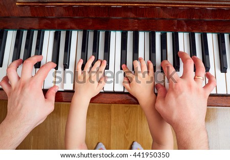 Top view close-up of hands of father and child on a piano keyboard. The parent teaches the kid to play the piano. The concept of education, children's education.